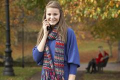 Teenage girl on mobile phone in autumn park with couple on bench in backgroun Stock Photos
