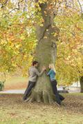 Romantic teenage couple by tree in autumn park Stock Photos