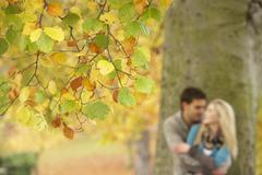 Shallow focus view of romantic teenage couple by tree in autumn park Stock Photos