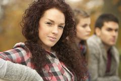 close up of group of teenage friends in autumn park - stock photo
