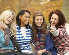 group of four teenage girls taking picture with camera sitting on bench in au - stock photo