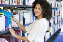 Woman in library pulling a book off a shelf (depth of field) - stock photo