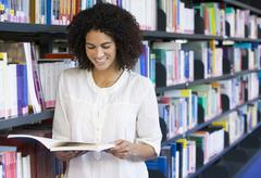Woman in library reading book (depth of field) Stock Photos