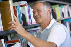 Man in library pulling book off a shelf (depth of field) - stock photo