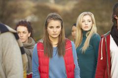 Teenage girl surrounded by friends in outdoor autumn landscape Stock Photos