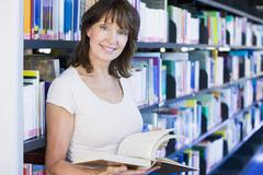 Woman in library holding book (depth of field) - stock photo