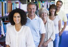 Five people in library standing by bookshelves (depth of field) - stock photo