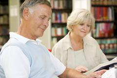 Man and woman in library reading (selective focus) Stock Photos