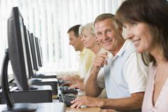 Four people sitting at computer terminals (selective focus/high key) - stock photo