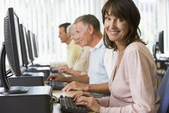 Four people sitting at computer terminals (depth of field/high key) - stock photo