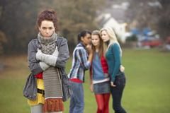 Upset teenage girl with friends gossiping in background Stock Photos
