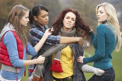 Group of female teenagers bullying girl Stock Photos