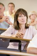 Woman sitting in adult classroom with students in background (selective focus) - stock photo