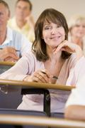 Woman sitting in adult classroom with students in background (selective focus) Stock Photos