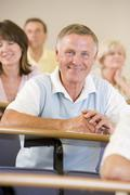 Man sitting in adult classroom with students in background (selective focus) - stock photo