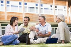 Adult students on lawn of school studying and talking - stock photo