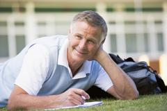 Adult student lying on lawn of school with notebook Stock Photos