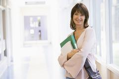 Woman standing in corridor with books (high key) - stock photo