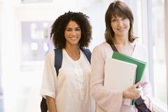 Two women standing in corridor with books (high key) Stock Photos