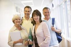 Four people standing in corridor with books (high key) Stock Photos
