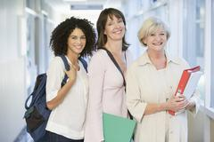 Three women standing in corridor with books (high key) Stock Photos