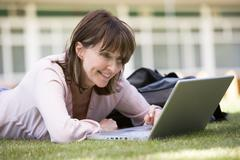 Woman lying on lawn of school with laptop - stock photo