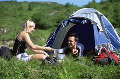 Couple outdoors at campsite with pots smiling (selective focus) - stock photo