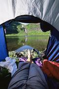 Man's legs in a tent overlooking scenic location - stock photo