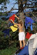 Woman outdoors at campsite hanging up wet clothes - stock photo