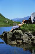 Woman outdoors at campsite sleeping on large rocks by lake - stock photo