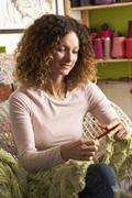 woman sitting in chair knitting - stock photo