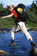 Woman outdoors hiking in scenic location jumping over water (selective focus) - stock photo