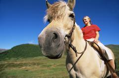 Woman outdoors riding horse and smiling (fisheye) Stock Photos