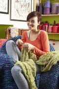 young woman sitting in chair knitting - stock photo