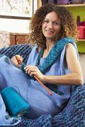 Close up of woman sitting in chair knitting Stock Photos