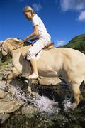 Woman outdoors riding horse through stream (fisheye) - stock photo
