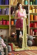 young woman knitting scarf standing in front of yarn display - stock photo