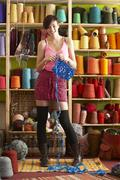 young woman holding knitting standing in front of yarn display - stock photo