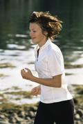 Woman outdoors by a stream running and smiling (selective focus) - stock photo