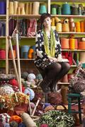 young woman sitting on stool holding knitting needles in front of yarn displa - stock photo