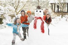 Stock Photo of family building snowman in garden