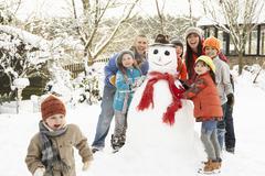 family building snowman in garden - stock photo