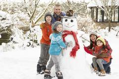 Family building snowman in garden Stock Photos