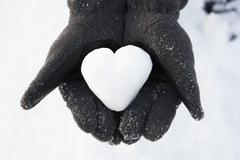close up of hands holding heart made out of snow - stock photo