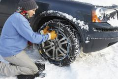 Man putting snow chains onto tyre of car Stock Photos