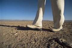 Man's legs walking through desert landscape Stock Photos