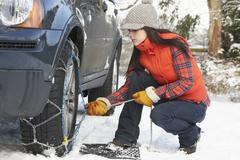 woman putting snow chains onto tyre of car - stock photo