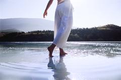 Woman's legs outdoors walking on water in scenic location (lens flare) Stock Photos