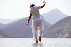 Woman outdoors walking on water in scenic location - stock photo