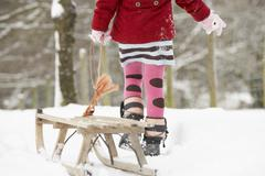 Close up of girl pulling sledge through winter landscape Stock Photos